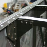 Floor stiffener riveted to firewall